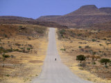 Single Figure Walking Down a Long Road in Namibia Photographic Print by Gianluca Colla