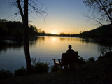 Man Sits on a Bench in Front of a Lake at Sunset Photographic Print by Hannele Lahti