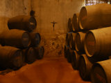 Stacked Up Wine Barrels and a Crucifix Photographic Print by Raul Touzon