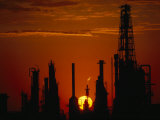 Oil Refinery Silhouetted During a Dramatic Sunset Fotografisk tryk af Paul Chesley
