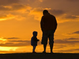 Father and His Baby Son Watch the Sunrise from a Coastal Hilltop Photographic Print by Jason Edwards