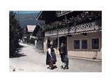 Two People Talk in the Street of the Alpine Village of Zeller See Photographic Print by Hans Hildenbrand