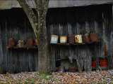 Old Rusted Cans Lined Up on a Shelf on the Side of a Barn Photographic Print by Steve Raymer