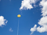 Yellow Smiley Face Parasail in Blue Skies with Nice Puffy Clouds Photographic Print by Mike Theiss