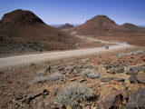Desolate Road Winds Between Hills in Namibia Photographic Print by Gianluca Colla