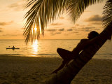 Woman Resting on a Palm Tree at Sunset, Sunset over the Caribbean Sea Photographic Print by Richard Nowitz