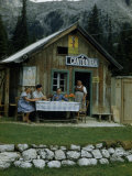Travelers Sit at a Table Outside Small Restaurant Near Mountain Pass Photographic Print by Volkmar K. Wentzel