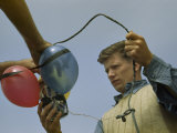 Man Holds Electrical Leads to Equipment Tied to Flotation Balloons Photographic Print by Robert Sisson