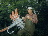 Fishing Tackle Dealer Holds Giant Fly, an Advertisement for His Shop Photographic Print by Andrew Brown