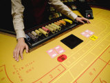 Dealer at a Hotel Casino Awaits Players for a Game of Baccarat Photographic Print by  xPacifica