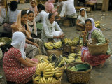 Vendors Sit Beside Bananas, a Customer Crouches with Empty Basket Photographic Print by W. Robert Moore