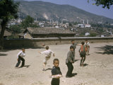 Boys Play Soccer in Sandy Yard Overlooking Rooftops Photographic Print by Dr. Gilbert H. Grosvenor