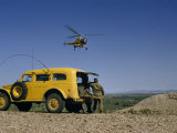 Serviceman Watching Hovering Helicopter Stands Beside a Yellow Truck Photographic Print by Richard Hewitt Stewart