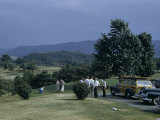 Men Stand and Talk Near Women Putting on a Golf Course Photographic Print by Walter Meayers Edwards