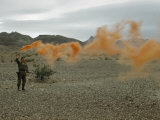 Man Shows Wind Direction with Smoke Grenade for Nearby Helicopter Photographic Print by Richard Hewitt Stewart