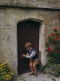 Boy Bounces a Ball in Front of a Wooden Door Bordered by Flowers Photographic Print by Melville Grosvenor