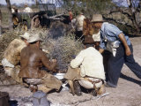 Cowboys Crouch around Campfire to Eat as Cook Continues to Work Photographic Print by Howell Walker