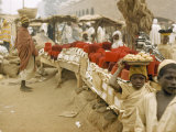 Boys Walk Past a Fez Vendor's Table in an Open-Air Market Photographic Print by Dr. Gilbert H. Grosvenor