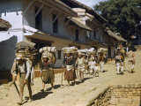 Hill People Carrying Enormous Loads Walk into a Town Photographic Print by Volkmar K. Wentzel