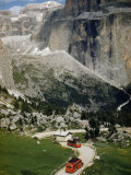 Steep Cliffs Tower over Red Buses on Narrow Road Through Mountains Photographic Print by Volkmar K. Wentzel