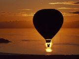 Riding in a Hot Air Balloon over Water at Sunset Photographic Print by Chris Johns
