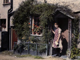 Girl Stands Outside Her Cottage Next to Her Garden Photographic Print by Clifton R. Adams