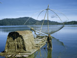 Fisherman Stands in Canoe Beside Raft with Hut and Fishing Net Photographic Print by Joseph Baylor Roberts