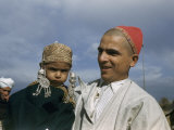 Smiling Father Holds His Frowning Son Photographic Print by Volkmar K. Wentzel