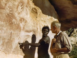 Aboriginal Man Pointing to Rock Art Talks to Researcher Photographic Print by Howell Walker