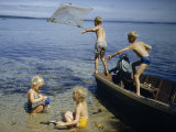 Children Play in a Boat and in the Water at the Edge of Higgins Lake Photographic Print by Andrew Brown