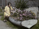 Woman Sits on a Boat Now Serving as a Flower Bed Photographic Print by Clifton R. Adams