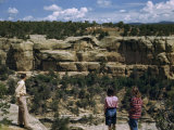 Tourists Stand on a Canyon Rim Overlooking Ancient Cliff Dwellings Photographic Print by Willard Culver