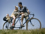 Man and Woman Straddling Tandem Bicycle Look at Child in Back Seat Photographic Print by B. Anthony Stewart