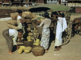 Vendors Pack Unsold Fruit into a Cart Photographic Print by W. Robert Moore