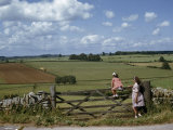 Two Girls Linger by a Wooden Gate Overlooking Fields Photographic Print by Melville Grosvenor