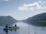 Men Paddle a Canoe Loaded with Gear across a Tranquil Lake Photographic Print by Andrew Brown