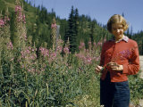 Teenage Girl Admires a Lush Stand of Fireweed Photographic Print by Ralph Gray