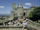Woman Sitting on Stone Wall Watches People Touring Castle's Ramparts Photographie par Walter Meayers Edwards