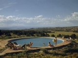 Vacationers Relax Beside Pool Overlooking Plain and Distant Mountains Photographic Print by Justin Locke
