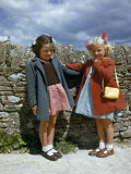 Schoolgirls in Cloth Coats Stand by a Stone Wall on a Windy Day Photographic Print by Melville Grosvenor