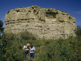 Two Boys Stand Below a Sandstone Butte Called Pompeys Pillar Photographic Print by Ralph Gray