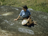 Woman Inspects Ancient Petroglyphs Carved into Volcanic Rock Photographic Print by Richard Hewitt Stewart