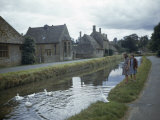Girls Watch Ducks Swim in a Millstream Lined with Stone Cottages Photographic Print by Melville Grosvenor