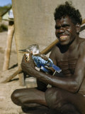 Smiling Man Holds a Captive Kookaburra Photographic Print by Howell Walker
