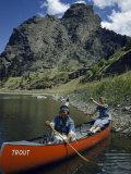 Teenage Girls Paddle a Canoe on Missouri River Near Rocky Cliffs Photographic Print by Ralph Gray