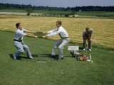 Men Pull on Turf of Combined Grasses to Show its Strength Photographic Print by Jack Fletcher
