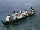 Passengers of an Outrigger Canoe Stand, Sit, Squat in the Narrow Boat Photographic Print by W. Robert Moore