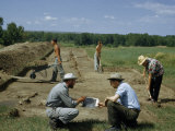 Archeologists Confer While Assistants Dig and Carry Away Dirt Photographic Print by Ralph Gray