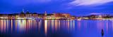 Edificios en la orilla iluminados al atardecer, Estocolmo, Suecia Lámina fotográfica por Panoramic Images,