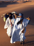 Berber Tribesmen Lead their Camels Through the Sand Dunes of the Erg Chegaga, in the Sahara Region  Photographie par Mark Hannaford